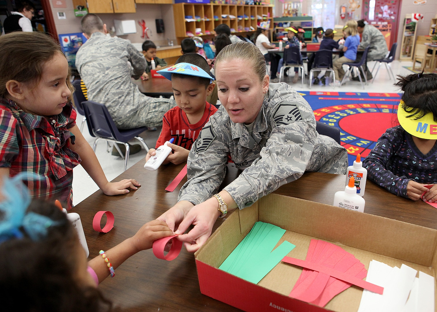 Master Sgt. Christy Hayes, Air Force Intelligence, Surveillance and Reconnaissance Agency, helps Valley Hi Elementary School kindergarten students make a paper chain Dec. 1. Airmen from AFISRA adopted the classroom through the Joint Base San Antonio adopt-a-school program. (U.S. Air Force photo/Robbin Cresswell)