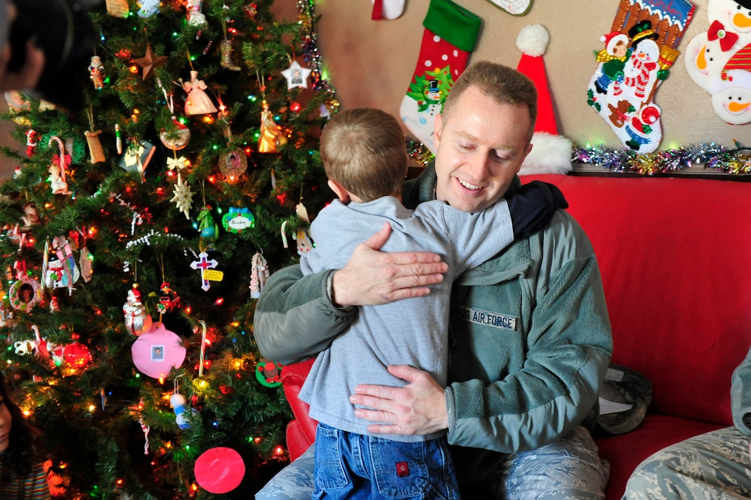 Master Sgt. Drue Titensor, 419th Aircraft Structural Maintenance supervisor, gets a hug at the home of a foster family as he delivers gifts Dec. 15. (U.S. Air Force photo/Kim Cook)
