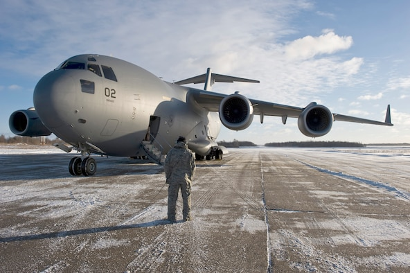 U.S. Air Force Tech. Sergeant Joseph Johns, flying crew chief from Papa, Hungary communicates with the C-17 Globemaster III pilots while on an airfield in Lithuania, Dec. 10, 2010.  The three-day mission will span over 7000 miles covering countries of Hungary, Poland, Afghanistan and Lithuania with over 75,000 tons of cargo.  (U.S. Air Force photo/TSgt Wayne Clark) (Released)