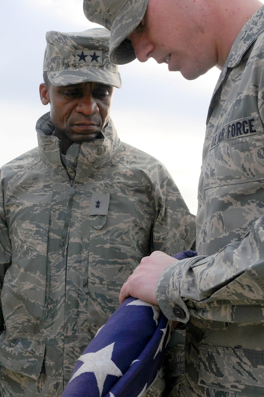Maj. Gen. Darren McDew, Air Force District of Washington commander, listens to Airman 1st Class Robert Matthews, AFDW ceremonial guardsman, describe the precision put into every American flag folded by honor guard members, Dec. 21, on Joint Base Anacostia-Bolling. General McDew visited fellow 11th Operations Group and AFDW Airmen for his first time as commander and later coined Airman Matthews for his flawless description of his team members. (U.S. Air Force photo by Senior Airman Steele C. G. Britton)