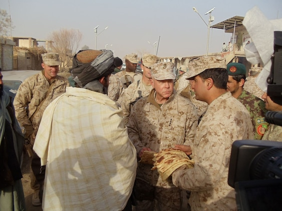 The commandant of the Marine Corps, Gen. James F. Amos, visits with locals at the bazaar in Marjah, Afghanistan, Dec. 24, 2010.