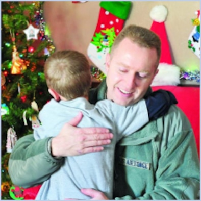 """Master Sgt. Drue Titensor, 419th Aircraft Structural Maintenance supervisor, gets a hug Dec. 15 during the Utah Foster Care Foundation """"Christmas Tree"""" event.  (U.S. Air Force photo by Kim Cook)"""
