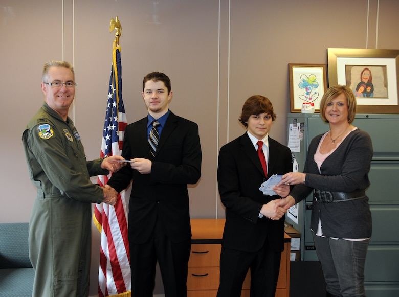 Buffalo Stars Hockey Team Captain Jeff Welch (on left) presents 107th Airlift Wing Commander Col. Jim McCready and team member Nick Radwan presents 107th Family Support Coordinator Jeanne Goetze with gift cards to local department and grocery stores.
