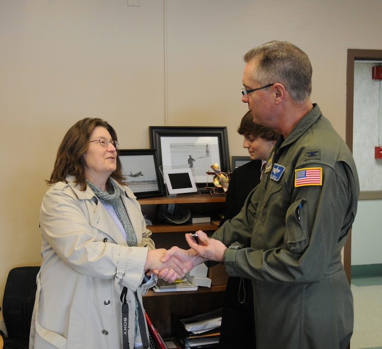 "Col. Jim McCready the 107th Airlift Wing Commander presents a unit coin to Sandi Radwan a Buffalo stars event coordinator. Sandi Radwan along with the Buffalo stars organized a fundraiser that netted $1200 worth of gift cards to local grocery and department stores. The gift cards were then donated to the 107th Family Support. ""This is great timing,"" said Jeanne Goetze the 107th Family Support Coordinator. ""With Christmas coming, we have a list of members that can really use some help. These gift cards will really make a difference,"" she added."