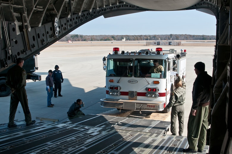 Jim McIlrath, Christ United Methodist Church pastor, Warner Robins, Ga., drives a donated fire truck into the belly of a C-17 guided by members of the Air Force Reserve's 315th Airlift Wing, Charleston, S.C. The 315th AW C-17 landed Dec. 30, 2010, at Robins Air Force Base, Ga., to pick up humanitarian aid bound for Managua, Nicaragua. A 1984 E-One fire truck and medical supplies, totaling nearly 3.5 tons, was donated by Emergency Response Services for Latin America to assist countries in Latin America. (U.S. Air Force photo/Staff Sgt. Alexy Saltekoff)