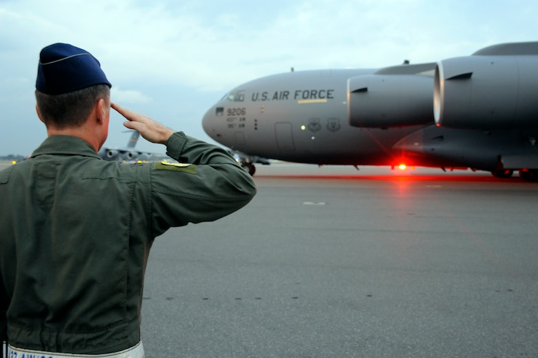 Air Force Col. John Wood salutes Brig. Gen. Carlton D. Everhart II as he taxis the newest C-17 Globemaster III aircraft on the Joint Base Charleston, S.C., flightline Dec. 22, 2010. The arrival of the aircraft brings the total number of C-17s assigned to the 437th Airlift Wing to 59. General Everhart is the 618th Air and Space Operations vice commander and Colonel Wood is the 437th AW commander. (U.S. Air Force photo/Staff Sgt. Marie Brown)
