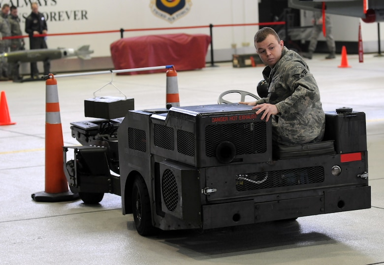 SPANGDAHLEM AIR BASE, Germany – Senior Airman Malcom Hart, 52nd Aircraft Maintenance Unit weapons load crew member, backs away after hanging a package on a pole while driving an MJ-1 during the Jammer Driver of the Year competition Dec. 28. Winners of the Jammer Driver of the Quarter competitions from the 2010 year competed in the event for the title of Jammer Driver of the Year. The winners of the Load Crew of the Year, and the Jammer Driver of the Year, will be announced during the Annual Awards Ceremony. (U.S. Air Force photo/Airman 1st Class Matthew B. Fredericks)