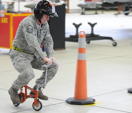 SPANGDAHLEM AIR BASE, Germany – Master Sgt. Chambliss McKendree, 52nd Aircraft Maintenance Squadron weapons flight chief, navigates a course of road cones on a small bicycle during an intermission between the Load Crew of the Year and Jammer Driver of the Year competitions. Sergeant McKendree competed against fellow Weapons Flight Chiefs to see who could navigate the course in the fastest time. The winners of the Load Crew of the Year, and the Jammer Driver of the Year, will be announced during the Annual Awards Ceremony. (U.S. Air Force photo/Airman 1st Class Matthew B. Fredericks)