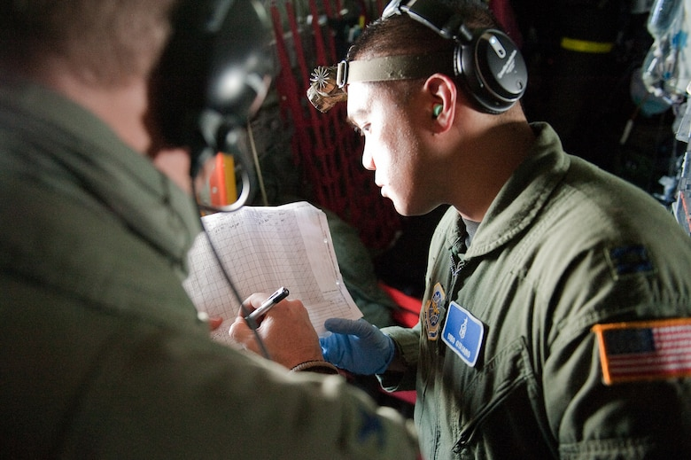CINCINNATI, OHIO -- Col. Todd Carter (left), an Air Force medical instructor, helps Capt. Dino Quijano annotate patient records during an aeromedical training exercise over the skies of southern Ohio on Feb. 11, 2010. Captain Quijano, a nurse from the 60th Inpatient Squadron at Travis Air Force Base, Calif., was participating in a two-week Critical Care Air Transport Team course designed to provide medical personnel with total immersion in the care of severely injured patients. Ground training and simulated-flight training are conducted at the University of Cincinnati, one of four Air Force Centers for Sustainment of Trauma and Readiness Skills (CSTARS) nationwide, but the final day of instruction is provided while airborne in a Kentucky Air Guard C-130. Kentucky's 165th Airlift Squadron began providing C-130s to use as a CSTARS training platform in 2009. (U.S. Air Force by Maj. Dale Greer)