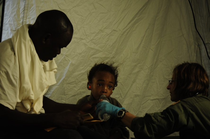 A six-year-old Haitian boy is given water by a medical technician with 1st Special Operations Support Squadron at the Toussaint Louverture International Airport in Port-au-Prince, Haiti, Jan. 19, 2010. The boy will be airlifted to a hospital in southern Florida. (U.S. Air Force photo by Tech. Sgt. James L. Harper Jr./Released)