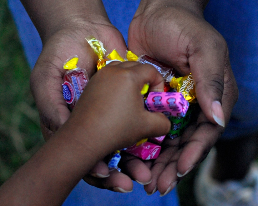 Team Soto Cano members pass out candy during a Chapel Hike Jan. 23 in Cinacla, Honduras. The members from Soto Cano Air Base, Honduras hiked nearly four miles carrying more than a ton of food and supplies to the remote community of 300. (U.S. Air Force Photo/Staff Sgt. Bryan Franks)