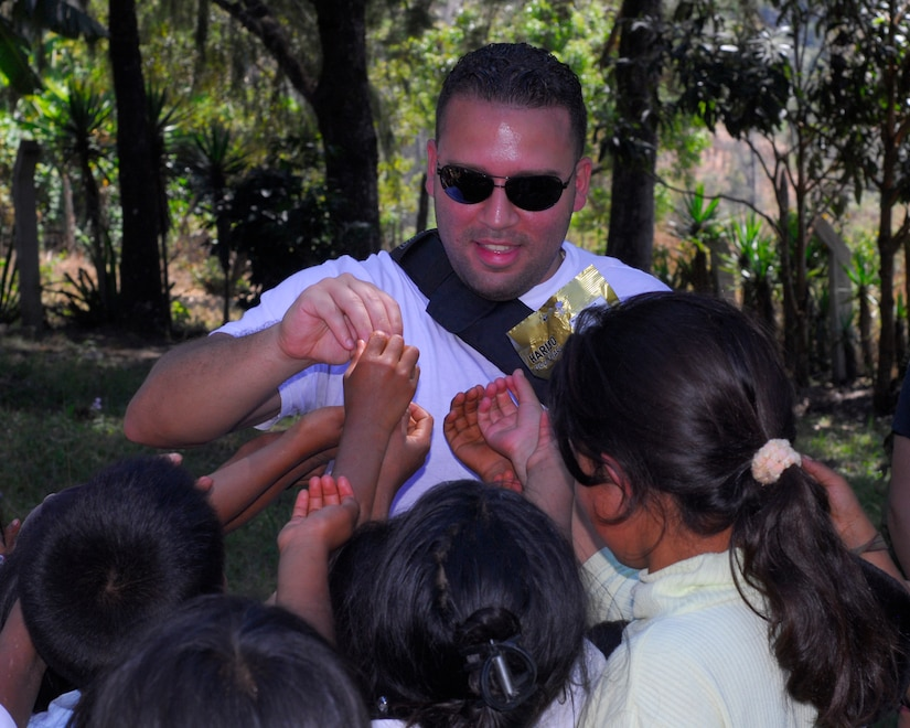 Staff Sgt. Israel Delvalle, 612th Air Base Squadron, passes out candy to the children of Cinacla, Honduras during a Chapel Hike Jan. 23. More than 70 Team Soto Cano members carried more than a ton of food and supplies nearly four miles to the remote community of 300. (U.S. Air Force Photo/Staff Sgt. Bryan Franks)