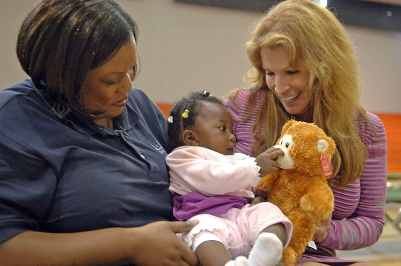 Francis Dugue (left) holds 6-month-old evacuee Anaellen Jean Louis as she plays with a teddy bear donated by Michele Gillen Jan. 24, 2010, at Homestead Air Reserve Base, Fla. Mrs. Gillen donated 2,500 of the bears to children of displaced evacuees at Homestead ARB and other places in the Miami area on behalf of Bear Hugs for Haiti. Mr. Dugue is a Miami-Dade 311 government center Memployee. Mrs. Gillen is an an WFOR-TV Miami chief investigative reporter. (U.S. Air Force photo/Tech. Sgt. Andy Bellamy)