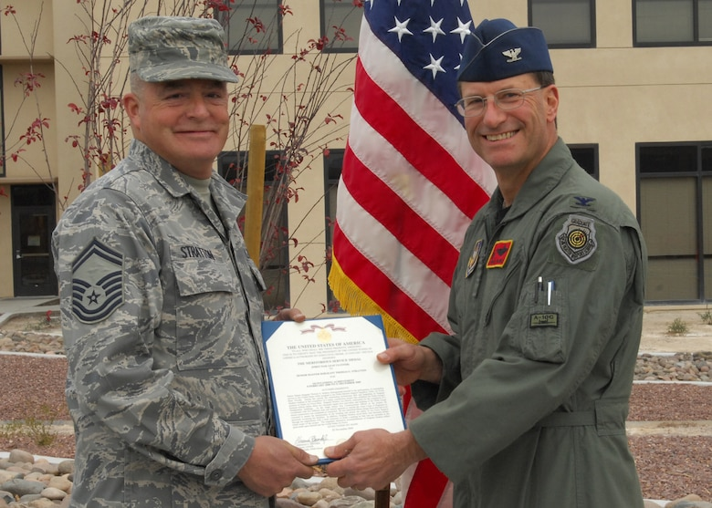 Col. Herman Brunke, 926th Group commander (right), presents Senior Master Sgt. Thomas Stratton, 926th Mission Support Squadron supply management superintendent, with a meritorious service medal during the group's building ribbon cutting ceremony Jan. 8. As the group's building custodian, Sergeant Stratton was instrumental to the $14.5 million renovation project. (U.S. Air Force photo/Staff Sgt. Erin Worley)