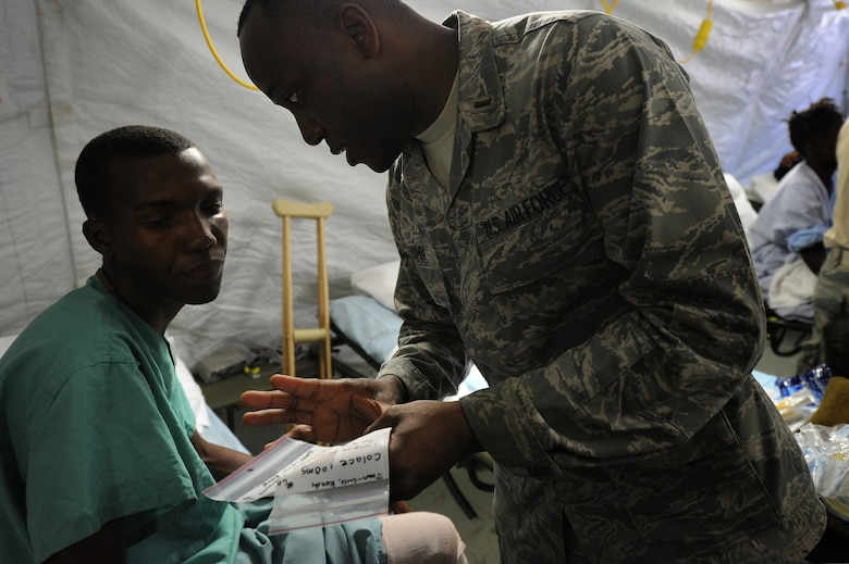 PORT-AU-PRINCE, Haiti - Airmen attached to Air Force Expeditionary Medical Squadron, Four Three Six, from Travis AF Base, Sacramento Cali., and Navy Corpsman treat earthquake survivors at an expeditionary medical facility located along the harbor of Port-au-Prince, Haiti February 3, 2010. A 7.0 earthquake Tuesday, January 12, left thousands of Haitians displaced, without access to food, water and vital medical care. (U.S. Navy Photo by Mass Communication Specialist 2nd Class Todd Frantom)