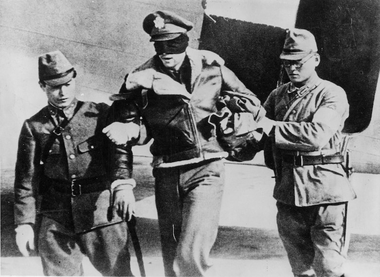 Lt. Hite, blindfolded by his captors, is led from a Japanese transport plane after he and the other seven flyers were flown from Shanghai to Tokyo. After about 45 days in Japan, all eight were taken back to China by ship and imprisoned in Shanghai. (U.S. Air Force photo)