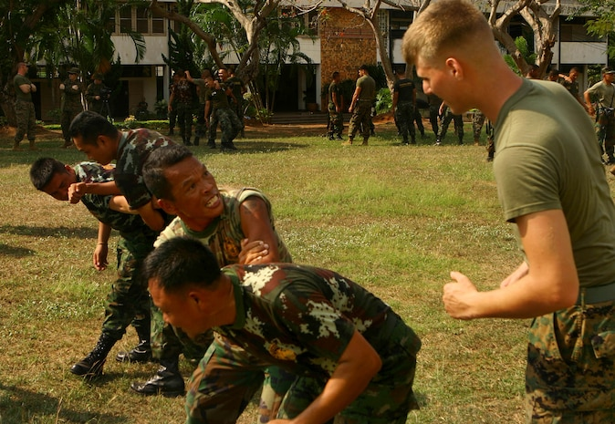 Cpl. Jeremy Hurlbert, a military policeman with Combat Logistics Battalion 31 (CLB-31), 31st Marine Expeditionary Unit (MEU), instructs a Royal Thai Marine on how to properly apply a non-lethal takedown move during a subject-matter expert exchange (SMEE) between Royal Thai security Marines and CLB-31, Feb. 5.  The MEU is currently participating in exercise Cobra Gold 2010 (CG' 10). The exercise is the latest in a continuing series of exercises design to promote regional peace and security.