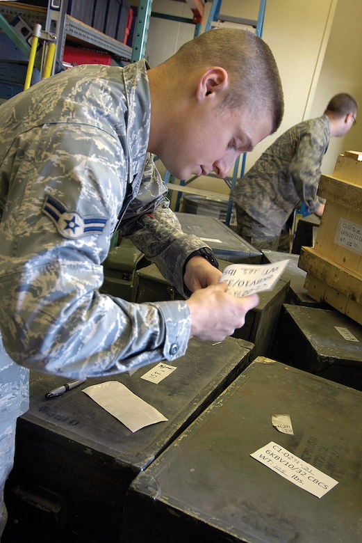 Airman 1st Class Taylor Neill, front, and Senior Airman Matthew Tackett, back, tag and record information on containers full of communications equipment that will go to Haiti with 32nd Combat Communications Squadron members when they deploy to help recovery efforts there. (Air Force photo by Margo Wright)
