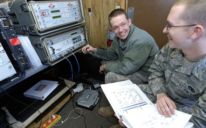 Exercises, war and areas hit by disaster need communications and members of the 3rd Combat Communications Group meet those challenges as a way of life. Airmen 1st Class Daniel Swann, left, and Zachary Taylor enjoy a quick joke while they test satellite communications equipment before it's packed for an exercise at Minot, N.D. (Air Force photo by Margo Wright)