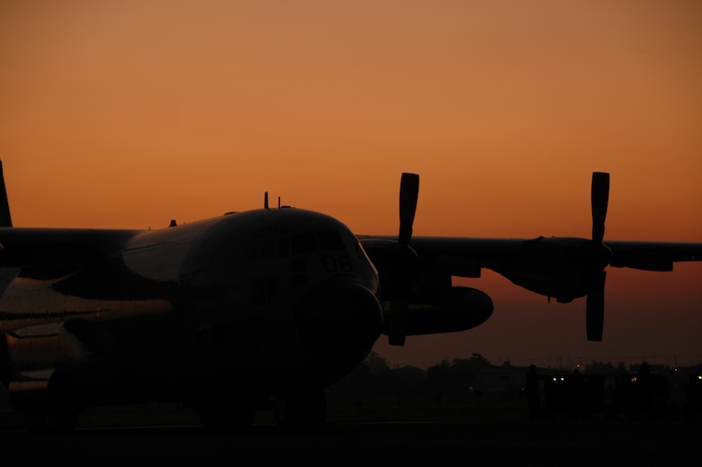 A Royal Thai Air Force C-130 is silhouetted by the sunset at Phitsanulok Royal Thai Air Force Base, Thailand, after a day of Modular Airborne Firefighting System training.   More than 50 members of the RTAF attended MAFFS training led by the Air Force Reserve's 302nd Airlift Wing, based at Peterson AFB, Colo.   Seven 302 AW members traveled to Thailand to provide expert training on safe and effective 