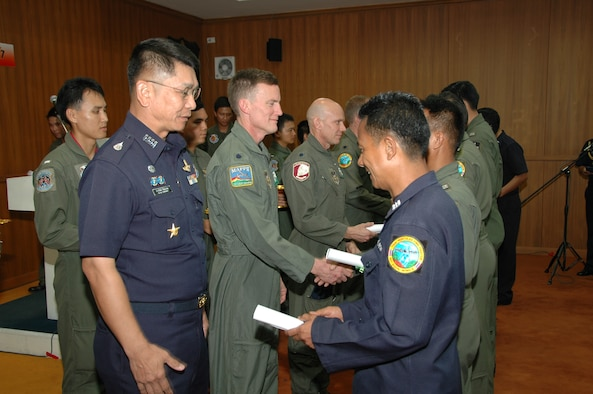 Special Group Captain (Brig Gen equivalent) Thawonwat Chantanagama, Deputy Director, Director of Operations, Royal Thai Air Force (left in blue), Lt. Col. Corey L. Steinbrink and Lt. Col. James M. Steward, with the Air Force Reserve's 302nd Airlift Wing present Modular Airborne Firefighting System training certificates.  More than 50 members of the RTAF attended the 302 AW-led training to increase their proficiency with the MAFFS system.  Seven 302 AW members traveled to Thailand to provide expert training on safe and effective C-130 MAFFS operations.  This event marks the first time the Air Force Reserve has sent delegates to train a foreign Air Force on use of the MAFFS equipment.  (U.S. Air Force photo/Capt. Jody L. Ritchie)