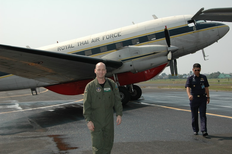 Chief Master Sgt. James D. Riley, chief loadmaster with the Air Force Reserve's 302nd Airlift Wing steps away from a PT-47, a modified version of the DC-3 at Phitsanulok Royal Thai Air Force Base, Thailand.  As a child, Chief Riley visited the same aircraft with his Thai neighbor.  The Chief returned to Thailand as one of seven members of the Air Force Reserve's 302 AW, based at Peterson AFB, Colo. to provide expert training to RTAF members on safe and effective C-130 MAFFS operations.  This event marks the first time the Air Force Reserve has sent delegates to train a foreign Air Force on use of the MAFFS equipment. (U.S. Air Force photo/Capt. Jody L. Ritchie)
