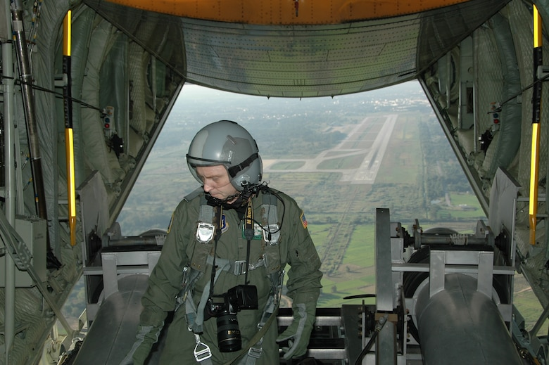 Chief Master Sgt. James D. Riley, chief loadmaster with the Air Force Reserve's 302nd Airlift Wing prepares to pull in the Modular Airborne Firefighting System tubes after take-off from the Phitsanulok Royal Thai Air Force Base, Thailand.   Seven members of the Air Force Reserve's 302 AW, based at Peterson AFB, Colo. were in Thailand providing expert training to RTAF members on safe and effective C-130 MAFFS operations.  This event marks the first time the Air Force Reserve has sent delegates to train a foreign Air Force on use of the MAFFS equipment. (U.S. Air Force photo/Capt. Jody L. Ritchie)