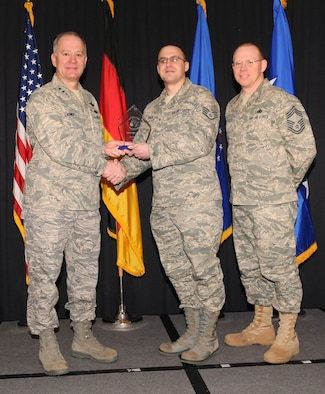 Maj. Gen. Ronald Ladnier, 17th Air Force Commander (left), and Chief Master Sgt. Steven Scott, acting 17th AF Command Chief (right), present the 2009 Airman of the Year award to Staff Sgt. Ehren Erks, (A6), during the annual awards breakfast Feb. 9.