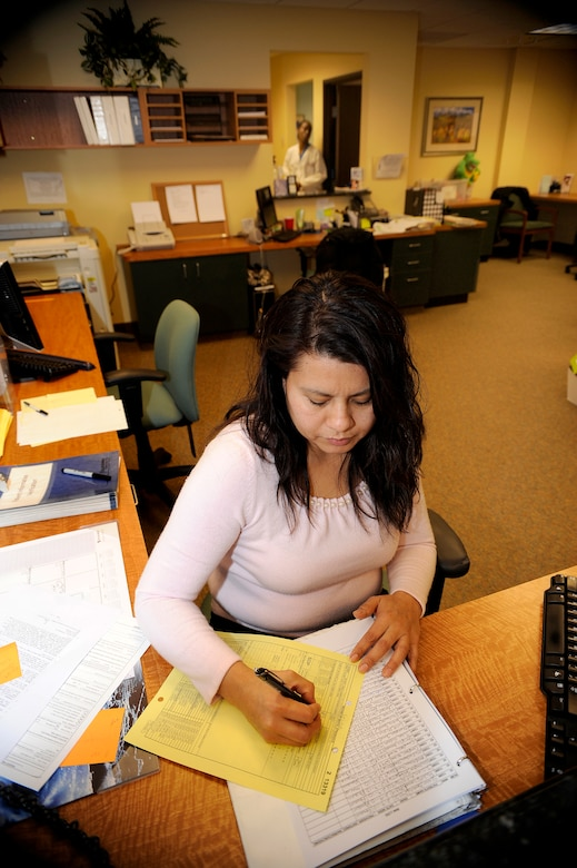 Receptionist Isabelle Gamboa fills out paperwork on new patients at Dentrust Dental Feb. 9. (U.S. Air Force photo by Staff Sgt. Steve Czyz)