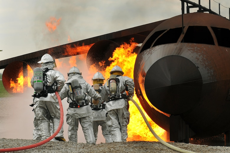 OFFUTT AIR FORCE BASE Neb.-- Offutt firefighters extinguish the flames in a simulated aircraft fire trainer during a joint training exercise here May 4. Firefighters from Offutt, Omaha's Eppley Airfield and guard and reserve units participated in the training exercise.