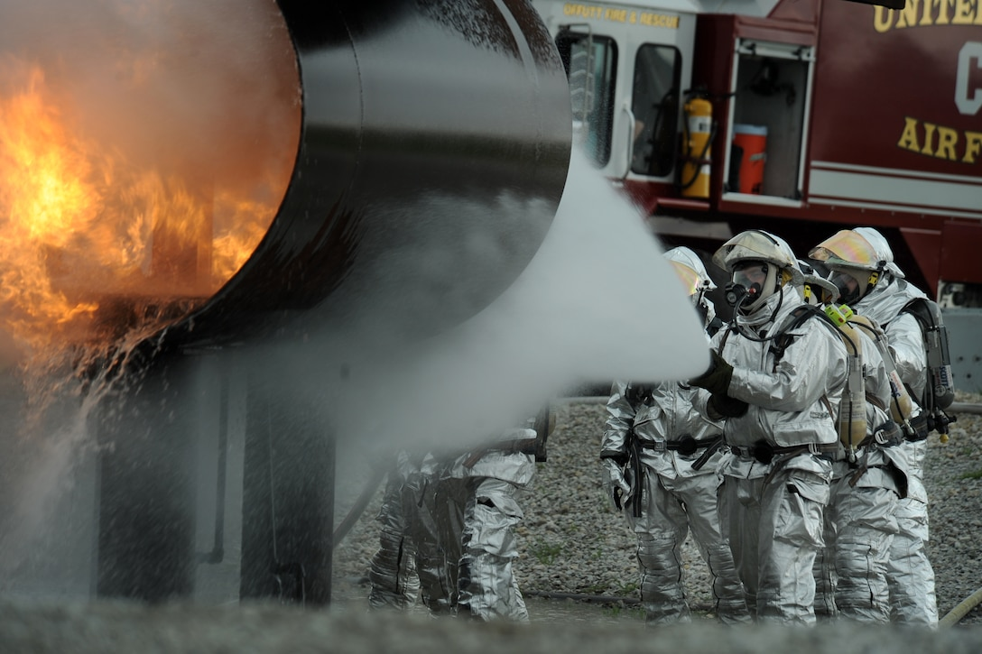 OFFUTT AIR FORCE BASE Neb. -- Offutt firefighters extinguish the flames in a simulated aircraft fire trainer during a joint training exercise here May 6. Firefighters from Offutt, Eppley airfield and guard and reserve units participated in the training.  U.S. Air Force photo by Josh Plueger