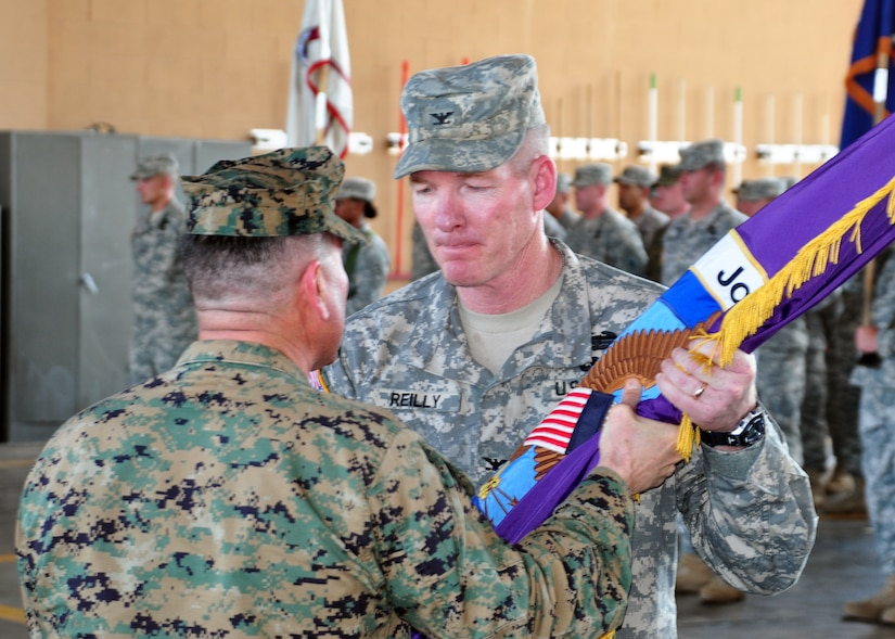 Army Col. Gregory Reilly accepts the colors and command of Joint Task Force-Bravo from the presiding officer Marine Corps Brig. Gen. David Garza, chief of staff, U.S. Southern Command, during a change of command ceremony at the Soto Cano Fire Department February 9. (U.S. Air Force Photo/Staff Sgt. Bryan Franks)