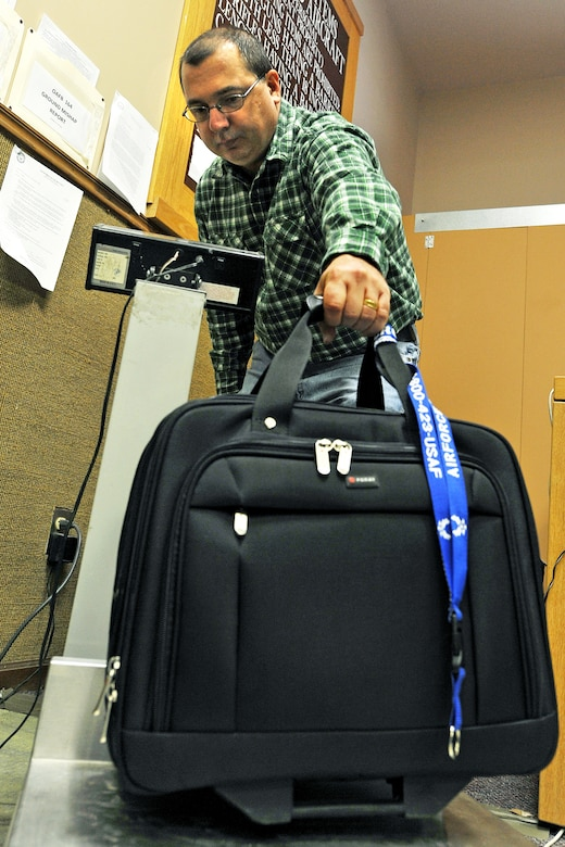 OFFUTT AIR FORCE BASE, Neb. -- Tom Kovy, logistics management specialist with the 55th Mission Support Group, weighs a piece of luggage at the passenger terminal here Feb. 11. Space-available flights for military members, family members, and military retirees to places such as Peterson AFB, Colo., Scott AFB, Ill., and Andrews AFB, Md., are available from Offutt. 