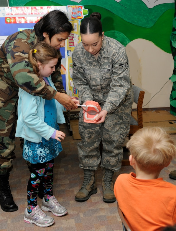 SPANGDAHLEM AIR BASE, Germany – Capt. Tonia Jhamb, left, and Airman 1st Class Ashley Ruiz, 52nd Dental Squadron, help Madelyne Comley, daughter of Tech. Sgt. Shaun Comley, 52nd Component Maintenance Squadron, show her first grade classmates the proper way to brush their teeth Feb. 9 at the Bitburg Elementary School. Each February, the American Dental Association sponsors National Children's Dental Health Month. In addition to visiting elementary and middle schools, the 52nd DS is opening the Spangdahlem Dental Clinic Feb. 27 to offer walk-ins for children up to 10 years of age. (U.S. Air Force photo/Airman 1st Class Staci Miller)