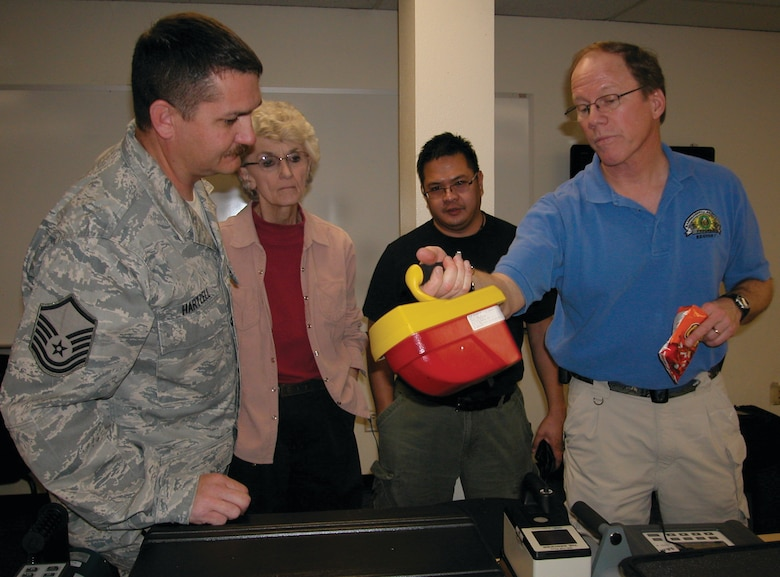 (from left) Master Sgt. Phillip Hartzell, Nancy Driscoll, Edward Crisostomo and Joel Swanson discuss a radiological detection device during a break in the presentation Swanson recently was giving on base. Swanson is a contractor response coordinator for the U.S. Department of Energy's Region 7, which includes all of California. March ARB first and emergency responders attended the session, which promoted interagency cooperation. (U.S. Air Force photo by Megan Just)