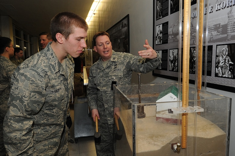 Capt. Jordan Hudak explains a display demonstrating the effects of earthquakes on buildings constructed atop soft ground to Cadet 4th Class Andrew Lankow during Majors' Night at the Air Force Academy Feb. 11, 2010. Captain Hudak is an instructor with the Department of Civil and Environmental Engineering. Cadet Lankow is assigned to Cadet Squadron 35. (U.S. Air Force photo/Rachel Boettcher)