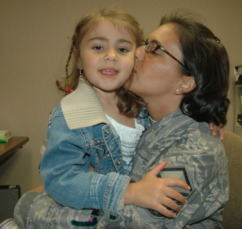 Master Sgt. Kara Stackpole, 439th Aeromedical Staging Squadron, gives a kiss to her daughter, Samantha, after the senior NCO's return from a deployment to Iraq in 2008.  (US Air Force photo/Tech. Sgt. Andrew Biscoe)