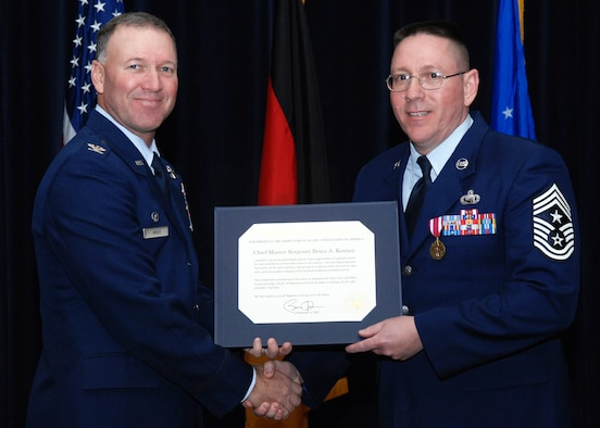 SPANGDAHLEM AIR BASE, Germany -- Retired Chief Master Sgt. Bruce Kenney, right, former 52nd Fighter Wing command chief, receives a presidential letter of appreciation from Col. Tip Wight, 52nd FW commander, during Chief Kenney's retirement ceremony Feb. 11 at Club Eifel. Chief Kenney served in the Air Force for 30 years. (U.S. Air Force photo/Airman 1st Class Nick Wilson)