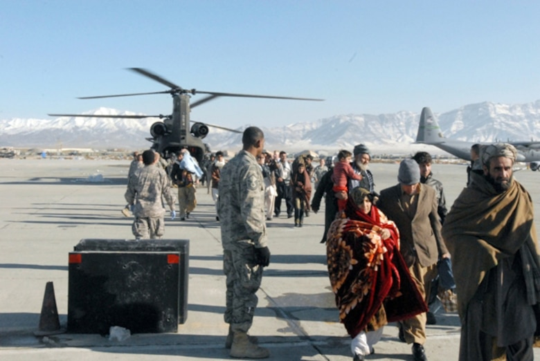 Avalanche evacuees exit a CH-47 Chinook helicopter at Bagram Airfield's flightline in Afghanistan, Feb. 9. Service members with Task Forces Cyclone, Falcon, Med. and the 455th Air Expeditionary Wing, medically assisted hundreds of people rescued from the avalanche stricken area while 380th Air Expeditionary Wing Airmen take control of the sky providing safety, security and air management during the joint-force humanitarian effort. (U.S. Army Photo/Spc. William Henry)