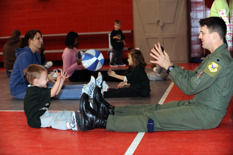 WHITEMAN AIR FORCE BASE, Mo. - Lt. Col. Jason Armagost, 13th Bomb Squadron commander, passes a soft basketball to his son Reece Armagost, during the Start Smart sports development activity Feb. 12, 2010.Whiteman Youth Center provides the Start Smart program to parents of children ages 3-to 5-years-old. The program provides parents the opportunity to bond with their children while teaching the children basic sports fundamentals. (U.S. Air Force photo/Tech. Sgt. Charles Larkin Sr)