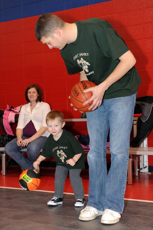 WHITEMAN AIR FORCE BASE, Mo. - Staff Sgt. Jeffrey Croteau (Right), 509th Aircraft Maintenance Squadron, and son Evan Croteau, practice dribbling basketballs during the Start Smart youth program Feb. 12, 2010. The program is provided for parents and children to spend quality time each week while participating in fundamental sports exercises including basketball, soccer, T-ball and flag football. (U.S. Air Force photo/Tech. Sgt. Charles Larkin Sr)
