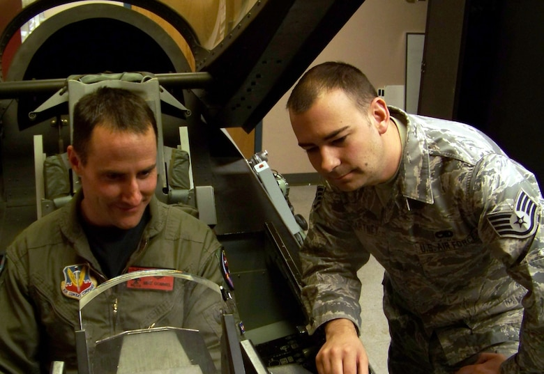 Staff Sgt. Jared McCartney, 120th Fighter Squadron, helps Maj. Michael Gommel egress an F-16 Fighting Falcon simulator. Sergeant McCartney is Team Buckley's Warrior of the Week for Feb. 15. (U.S. Air Force photo)