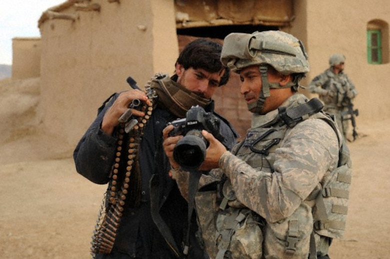U.S. Air Force Tech. Sgt. Efren Lopez, 4th Combat Camera Squadron, shows digital photographs to an Afghan soldier in Shabila Kalan, Zabul province, Afghanistan. (U.S. Air Force photo by Staff Sgt. Christine Jones)