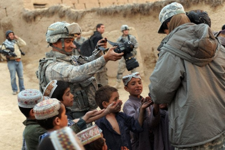 U.S. Air Force Tech. Sgt. Efren Lopez, 4th Combat Camera Squadron, takes a picture of Afghan children in Shabila Kalan, Zabul province, Afghanistan, Nov. 30, 2009. (U.S. Air Force photo by Staff Sgt. Christine Jones)