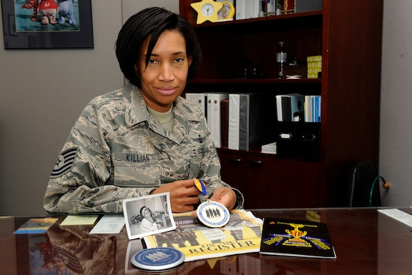 """Tech. Sgt. Monique Killian, 21st Space Wing Inspector General flight chief, wing readiness, holds the """"Unsung Hero"""" medal given to her mom, Ann Staples Shelton, Feb. 1, in Greensboro, N.C. at the 50th anniversary of the Greensboro sit-ins, which ignited the 1960s civil rights movement. Ms. Shelton, who passed away six years ago, was honored for her work during the sit-ins, which began with four college students at F.W. Woolworth Co. (Air Force photo by Craig Denton)"""