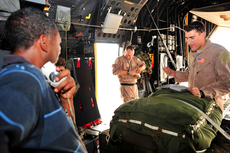 Ethiopian Air Force Capt. Hailu Teklu watches Senior Airman Jacob Dattage and Tech. Sgt. Darryl Woodruff perform a pre-flight inspection of equipment during his and five other Ethiopian Air Force officerssâ? visit to Camp Lemonnier February 8 - 12, 2010. The 81st Expeditionary Rescue Squadron conducted training on air drop procedures with the officers. (Photo by Petty Officer 2nd Class Joshua Bruns, Combined Joint Task Force - Horn of Africa)