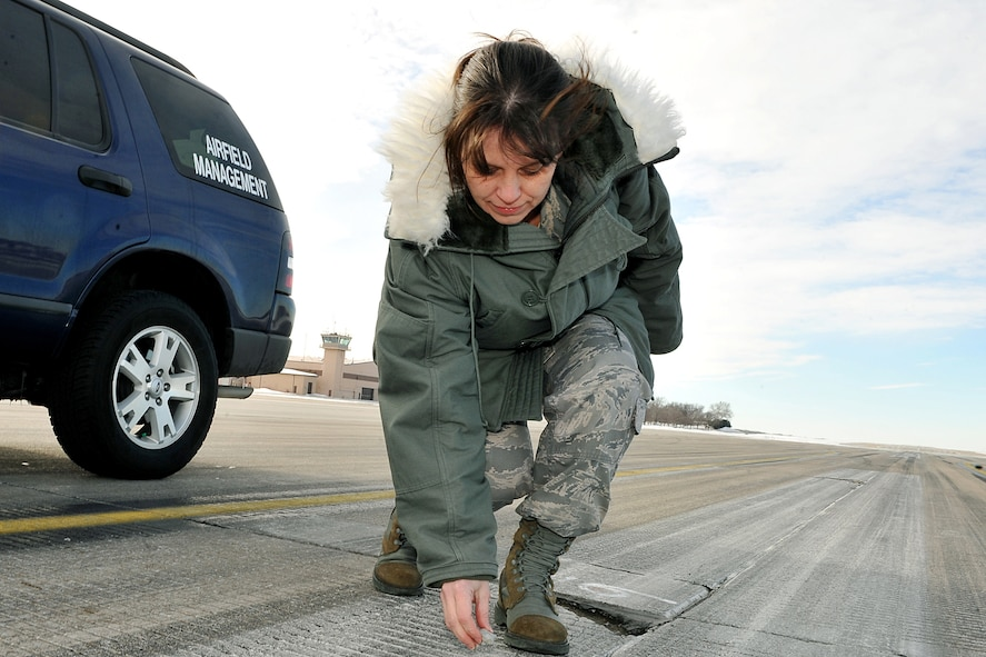 OFFUTT AIR FORCE BASE, Neb. - Senior Master Sgt. Laura Liedke, airfield manager with the 55th Operations Support Squadron, picks up a piece of foreign object debris on a taxiway here Feb. 16. The Airfield Operations Flight airfield management team coordinates with various base agencies to provide a safe environment for aircraft operations. 