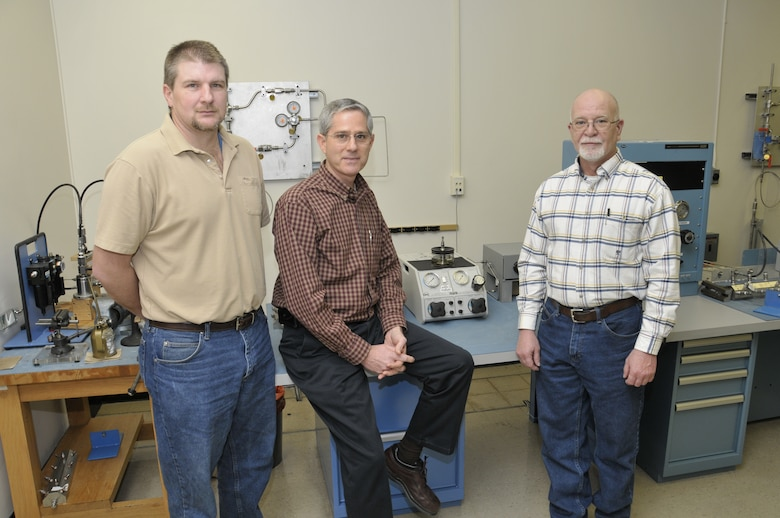 From left, Arnold Engineering Development Center's Precision Measurement Equipment Laboratory (PMEL) Brad Pearson, Dale West and Gary Fergus stand in front of where coworker Michael Bunch was working when the 49-year instrument technician had a heart attack Feb. 11. Bunch survived due to the quick response of the three men and base EMTs, security and the dispensary's nurse practitioner. (Photo by Rick Goodfriend)