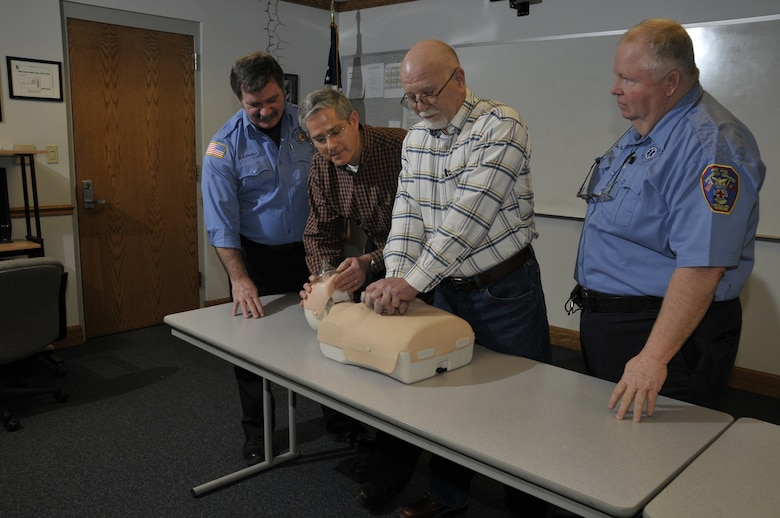 Far left and right Jim Phillips and Tim Mansfield, Aerospace Testing Alliance (ATA) paramedics with the Arnold Engineering Development Center Fire Department, watch as Precision Measurement Equipment Laboratory's Dale West and Gary Fergus demonstrate how they administered cardiopulmonary resuscitation (CPR) to a coworker, Michael Bunch, Feb. 11. Phillips and Mansfield were the two EMTs who responded to the 911 call placed that day by Brad Pearson, an ATA instrument technician in the lab. Mansfield is also a CPR instructor on base. Doctors told Bunch he should be able to return to work in about three weeks. (Photo by Rick Goodfriend)