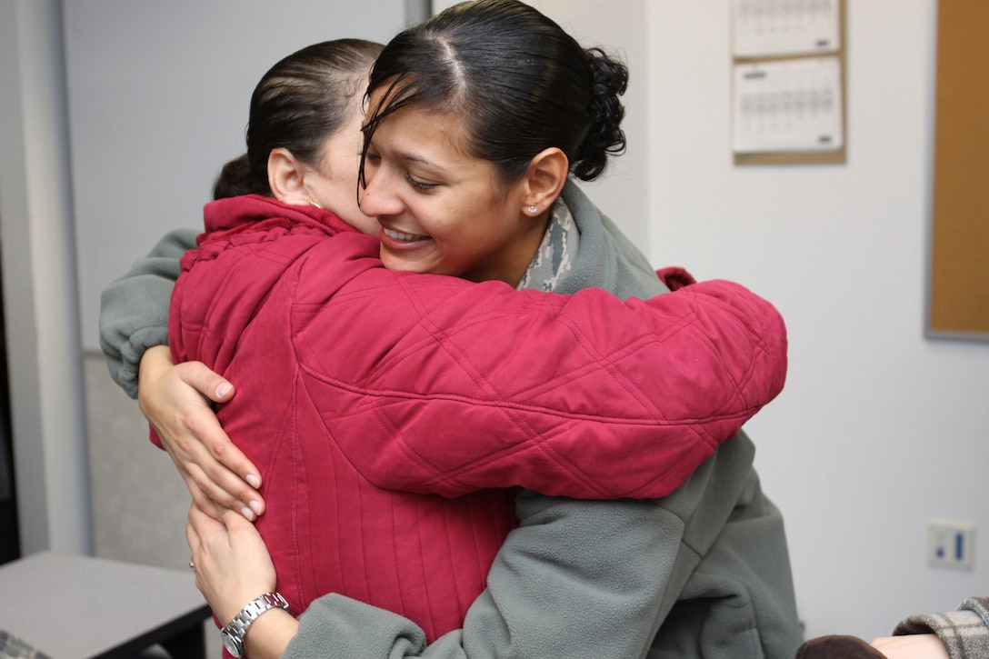 A picture of U.S. Air Force Senior Airman Erica Aybar-Morillo hugging her mother before deploying.